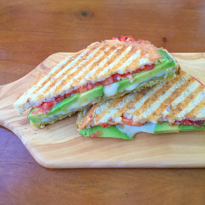 Avocado Cheese Panini. This mouthwatering sandwich combines creamy avocado, sun-ripened tomatoes, mozzarella cheese, and pesto. With only a handful of ingredients, it comes together quickly and easily, and tastes out of this world.