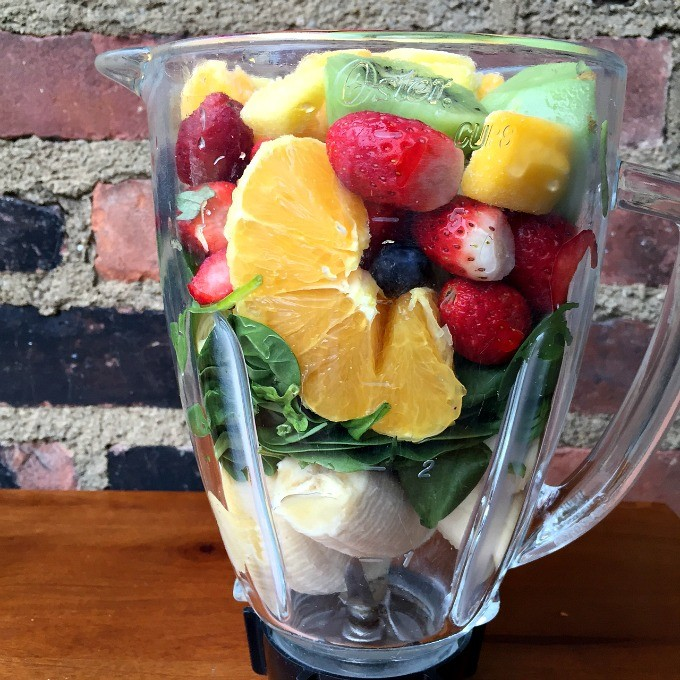 Fruit and Spinach Smoothie with Oranges, Strawberries, Banana, Raspberries, Kiwi and Mango